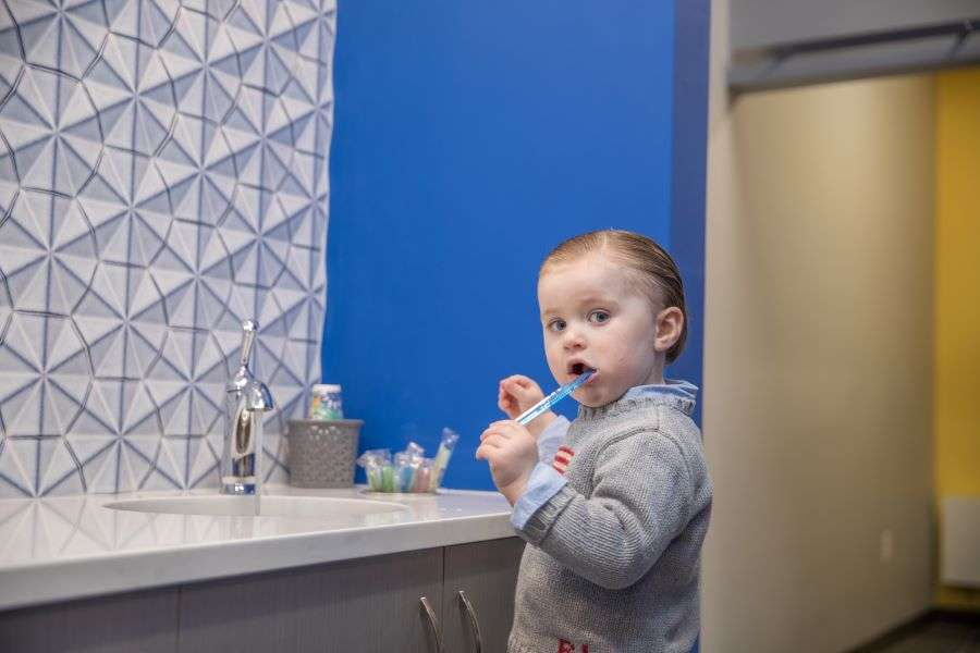 Young boy brushing his teeth at the dentist office